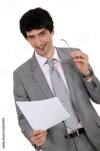 Businessman holding hiss glasses and sheet of paper
