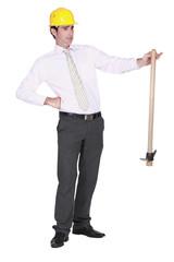 Architect sheepishly holding pick-axe