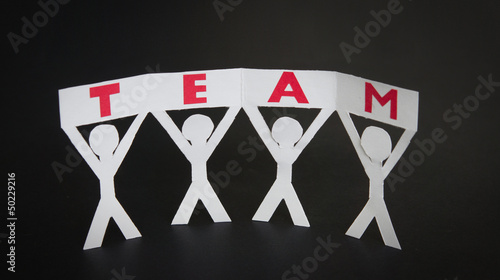 Paper silhouettes holding a Team sign