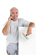 Smiling mature laborer on phone