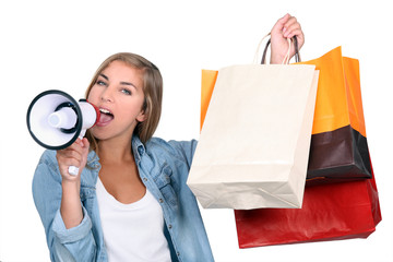 Woman holding shopping bags and shouting into a loudspeaker