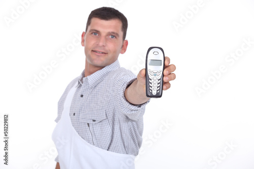 Dark haired man holding out mobile telephone