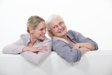 Two women on a white sofa