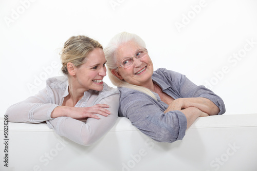 Two women on a white sofa