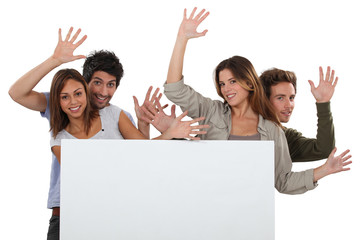 Enthusiastic friends with a board left blank for your message