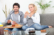 Couple having breakfast on couch
