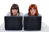 Two young women side by side with laptops