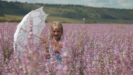 Little girl with lace parasol on meadow