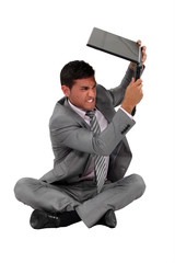 A businessman about to smash his laptop.