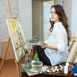 Female artist paints picture on canvas