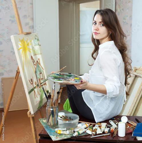 Female artist paints picture on canvas