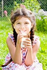 Девочка с йогуртом и ложкой в руках