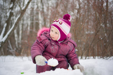 Adorable girl dig snow with small shovel in park