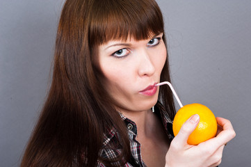 beautiful woman drinking a cocktail of orange