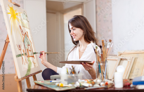 woman paints landscape on canvas