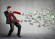 Leinwandbild Motiv Businessman attracts money with a large magnet