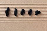 Five black pebbles on raked sand