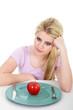 Junge blonde Frau frustriert bei Diät mit rotem Apfel