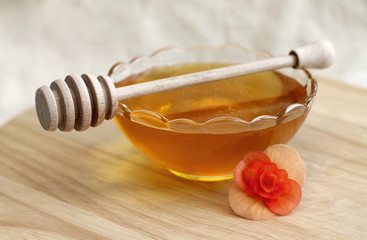 Bowl of honey with wooden drizzler, close-up