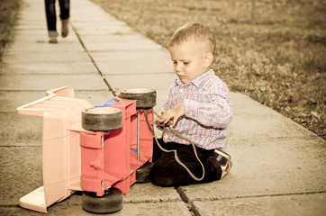 Small boy playing with a plastic truck