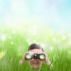 Man looking through binoculars from grass. Lots of copyspace. He