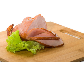 Baked ham with slices on wooden board on white background