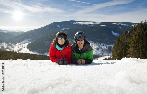 Young happy couple lying in snowy mountains. Winter sport