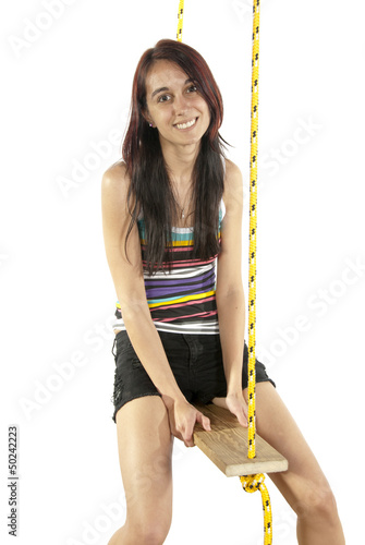 Happy pretty young girl swinging on a swing
