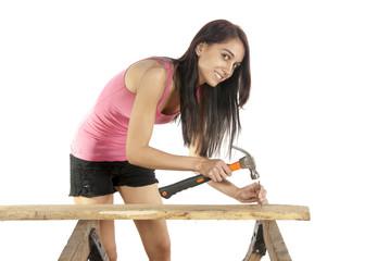 Young woman hammering nail into wood