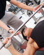 Young man lifting the barbell in the gym with instructor.