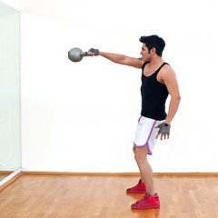 Young man training in the gym with heavy ball.