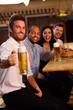 Happy man holding mug of beer in pub