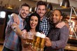 Group of happy friends clinking with beer in pub