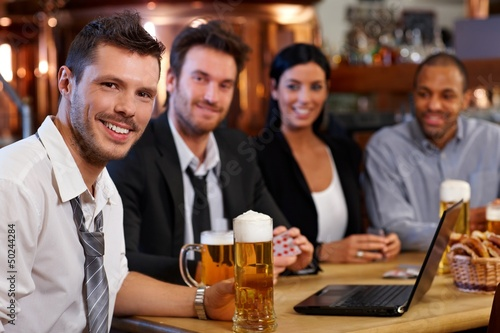 Young office worker drinking beer at pub