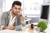 Desperate businessman sitting at desk in disorder poster