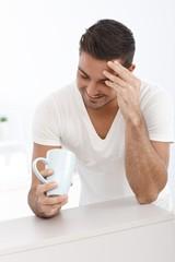 Happy man looking at tea mug
