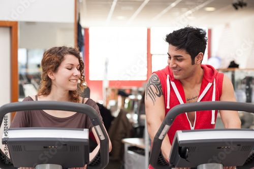 Young couple training in the gym with bike while talking