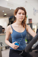 Young woman training in the gym with bike listening to music