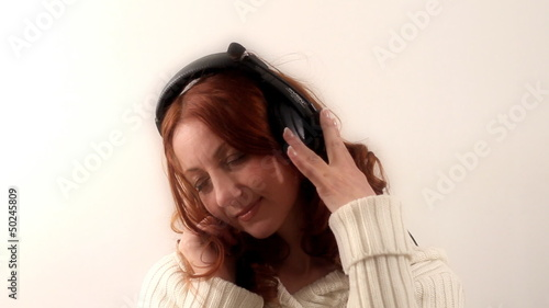 A girl listens music through headphones