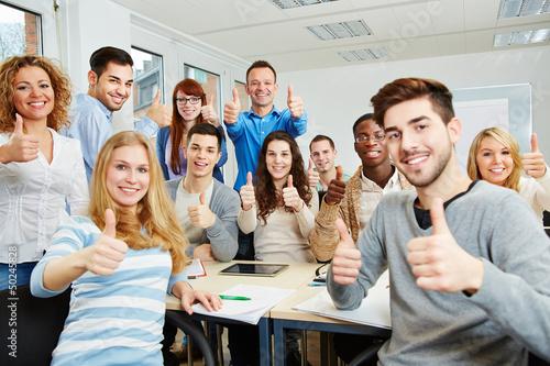 Studenten halten Daumen hoch in der Uni - 50245828