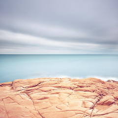Cliff rocks, blue ocean and cloudy sky background.