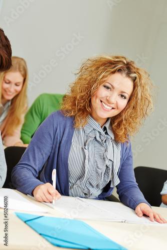 Lachende Frau sitzt im Lehrgang