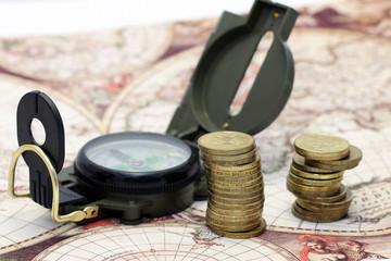 Золотые монеты и компас на фоне карты мира