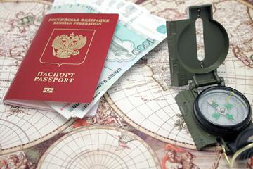 Паспорт, деньги и компас лежат на карте мира