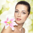Beauty face of young woman with flower. Beauty treatment concept