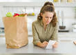 Concerned housewife checking bill after shopping in kitchen