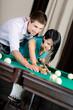 Man teaching woman to play billiards