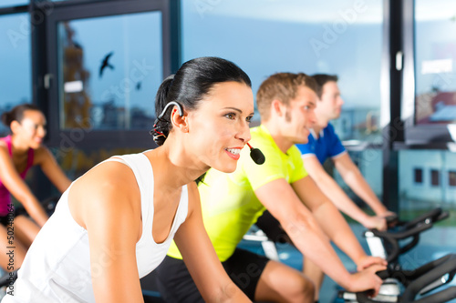 Group of people spinning on bikes in gym