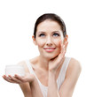 Woman putting on moisture cream from container on face
