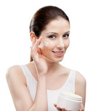 Woman applying moisture cream from container on face